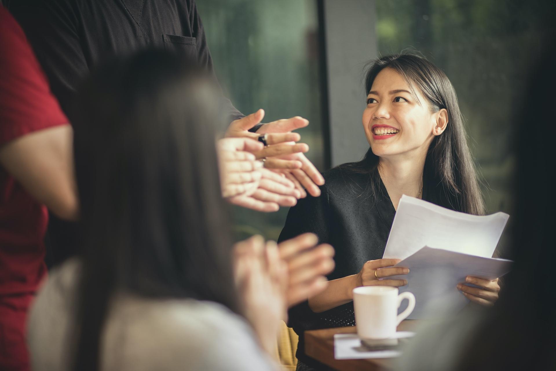 Frau bei einem Meeting, die glücklich lächelt